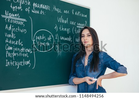 Portrait of english teacher writing on blackboard in classroom.