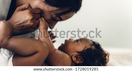 Portrait of enjoy happy love family african american mother playing with adorable little african american baby.Mom touching with cute son moments good time in a white bedroom.Love of black family