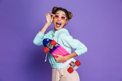 Portrait of european hipster girl with two buns in sunglasses smiling and holding skateboard isolated over violet background in studio