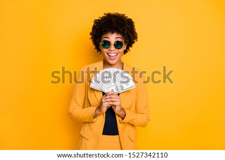 Portrait of excited afro american lady freelancer hold money fan get salary profit income scream wow omg wear style fashion jacket suit isolated over yellow color background