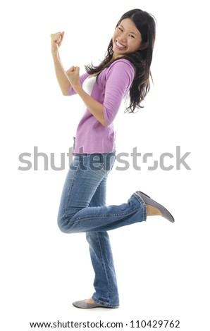 Portrait of excited Asian woman celebrating success over white background
