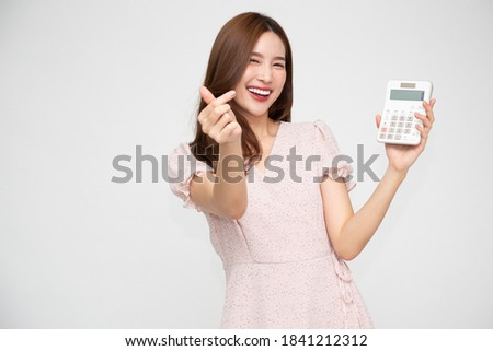 Portrait of excited Asian woman holding calculator isolated on white background, Business and financial concept
