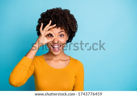 Portrait of excited astonished afro american girl show okay sign make binoculars watch look impressed scream wow omg wear stylish trendy sweater isolated over blue color background Stockfoto ©
