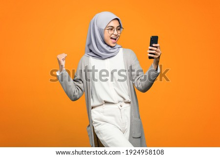 Portrait of excited beautiful Asian woman while looking at smartphone
