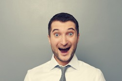 portrait of excited businessman over grey background