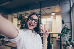 Portrait of excited cheerful smiling young pretty woman in spectacles making selfie photo and showing v-sign with two fingers
