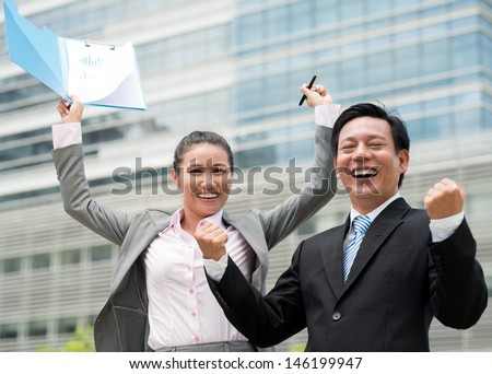 Portrait of excited co-workers showing fist at camera