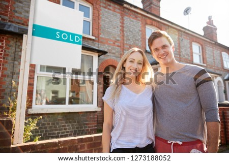 Portrait Of Excited Couple Standing Outside New Home With Sold Sign #1273188052