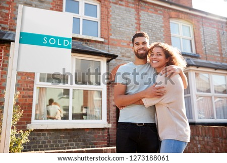 Portrait Of Excited Couple Standing Outside New Home With Sold Sign