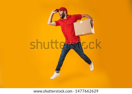 Portrait of excited delivery man in red uniform running and holding parcel box isolated over yellow background