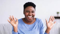 Portrait of excited emotional young curvy African American woman smiling and laughing looking at camera while sitting on the sofa at home in living room. Cheerful chubby lady posing, hearing good news