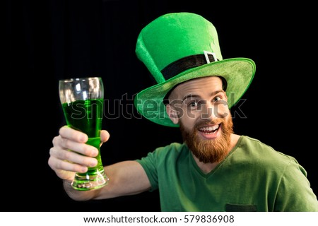 portrait of excited man holding glass of beer on St.Patrick's day isolated on black