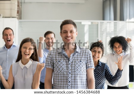 Portrait of excited millennial Caucasian businessman pose with young multiracial team motivated for success, smiling overjoyed business group together with male manager show team spirit and support