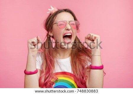 Portrait of excited overjoyed female model clenches fists with pleasure, screams in happiness, celebrates her victory, has great triumph. Fashionable woman gestures joyfully indoors. Success concept #748830883