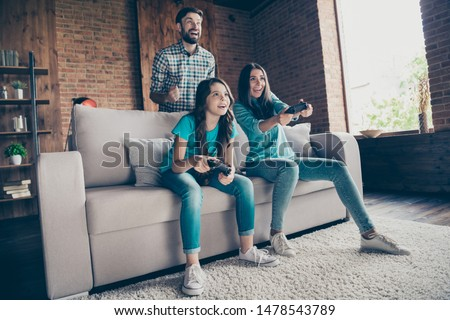 Portrait of excited people and little girl with brunet hair play videogame wearing denim jeans t-shirt sit divan in house indoors