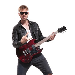 portrait of excited rockstar wearing sunglasses and leather jacket making rock on sign during concert while standing on white background
