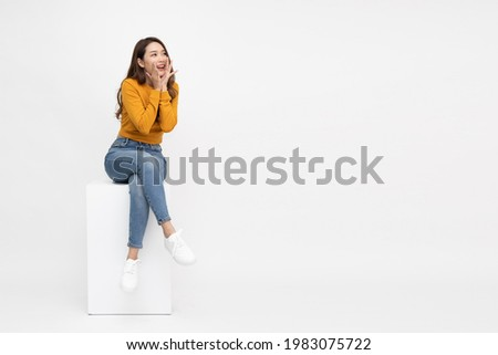 Portrait of excited screaming young asian woman sitting on white box isolated over white background, Wow and surprised concept Foto stock ©