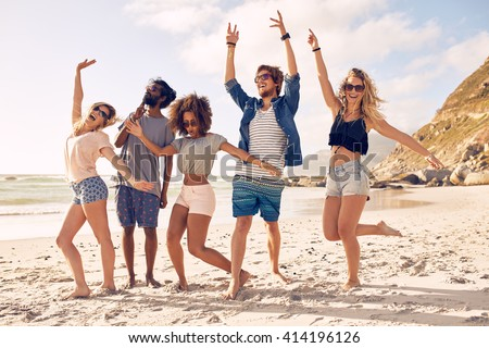 Portrait of excited young friends standing on the beach. Multiracial group of friends enjoying a day at beach.
