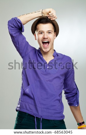 Portrait of excited young man wearing a hat celebrating success
