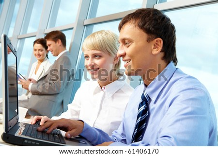 Portrait of executive partners looking at laptop display while working in office