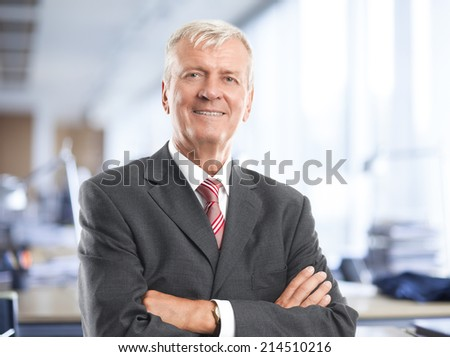 Portrait of executive senior businessman standing at office. Business people.