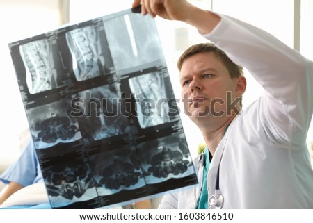 Portrait of experienced concentrated radiologist showing skiagram of back to sick woman. Doctor telling about improved results. Healthcare and medicine concept Stock photo ©