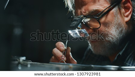 Portrait of experienced goldsmith working on a handmade jewelry ring with precious diamond stones in a workshop. Concept of jewelry, luxury, goldsmith, diamonds, brilliance.