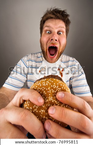 Portrait of expressive fat man eating burger - stock photo