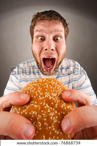 Portrait of expressive man eating juicy hamburger