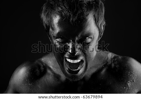 Portrait of expressive man painted with black color. Body painting project.