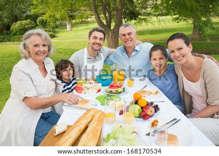 Portrait Of Extended Family Dining At Outdoor Table