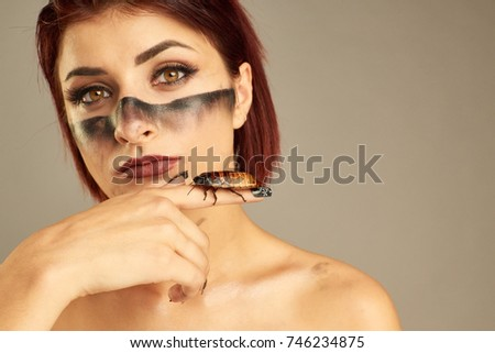 Portrait of Extravagant girl with cockroaches on her hand and bright make up #746234875