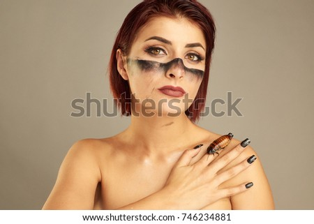 Portrait of Extravagant girl with cockroaches on her hand and bright make up #746234881