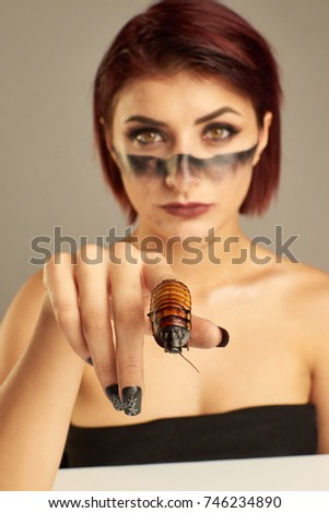 Portrait of Extravagant girl with cockroaches on her hand and bright make up #746234890