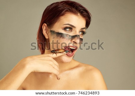 Portrait of Extravagant girl with cockroaches on her hand and bright make up #746234893