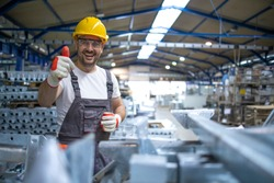 Portrait of factory worker in protective equipment holding thumbs up in production hall.