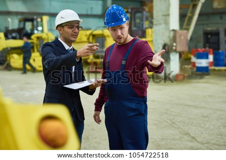 Portrait of factory worker talking to Middle-Eastern manager in workshop of modern plant, copy space