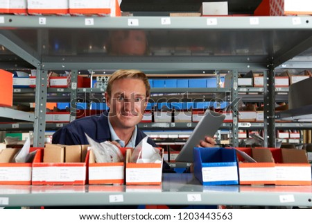 Portrait Of Factory Worker Using Digital Tablet In Store Room