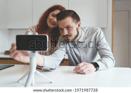 Portrait of family couple with smartphone and tripod involved in online conference. Happy couple sitting at modern house, man adjusting camera while discussing business plan at conference online