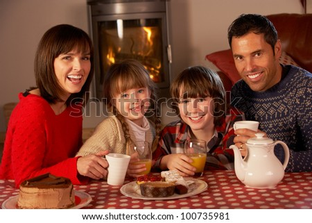Portrait Of Family Enjoying Tea And Cake By Cosy Log Fire