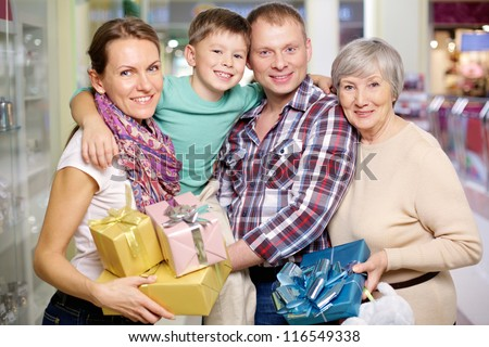 Portrait of family holding giftboxes in the shop