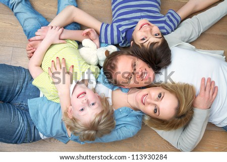 Portrait of family lying on floor in home