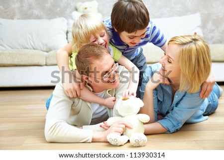 Portrait of family lying on floor living room and smiling to camera