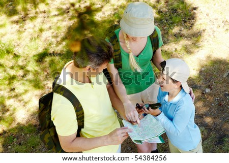 Portrait of family members looking at map in the forest at summer
