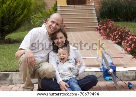 Portrait of family, mom and dad enjoying their son and airplane
