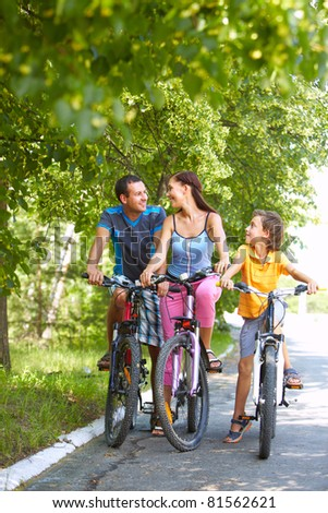 Portrait of family of three cycling in wood