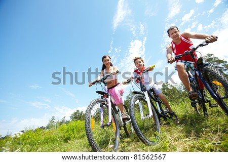 Portrait of family of three on bikes looking at camera
