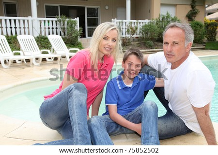 Portrait of family sitting by pool side