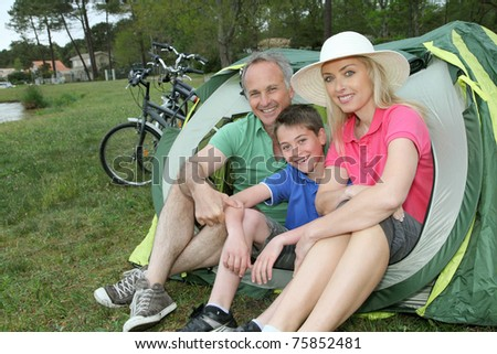 Portrait of family sitting in camping tent