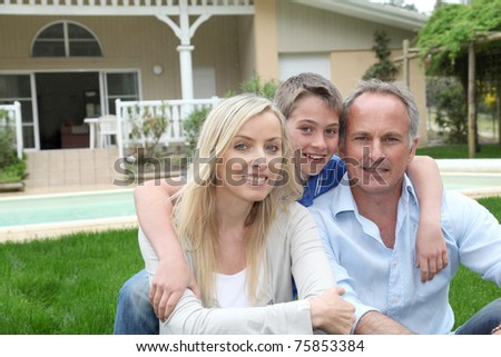 Portrait of family sitting in front of their house
